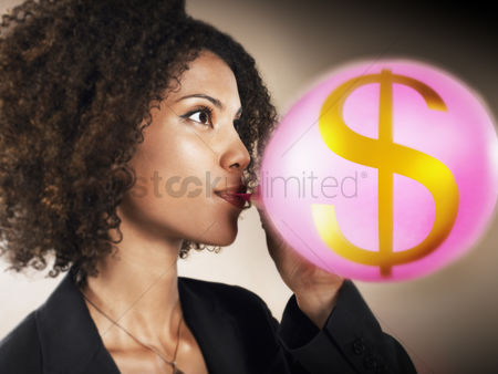 Blowing : Businesswoman blowing up balloon with dollar sign on head and shoulders