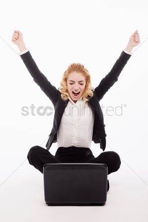 Celebrating : Businesswoman celebrating her success while using laptop