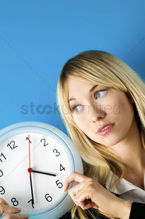 Wondering : Businesswoman holding a clock