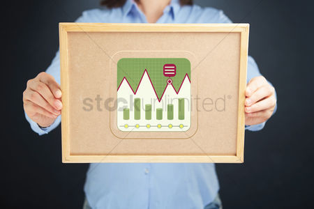 Cork board : Businesswoman holding a cork board with business infographic elements