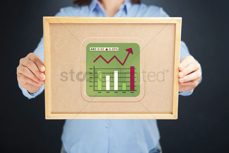 Cork board : Businesswoman holding a cork board with financial infographic elements