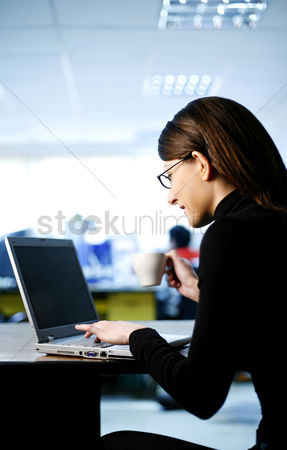 Internet : Businesswoman holding a cup of coffee while using laptop