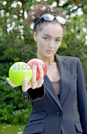 Composed : Businesswoman holding a green and a red ball