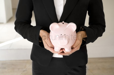 Business suit : Businesswoman holding a piggy bank