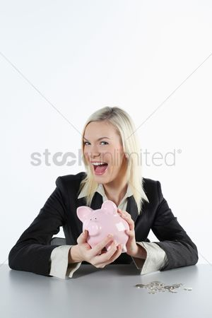 British ethnicity : Businesswoman holding a pink piggy bank