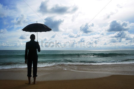 People : Businesswoman holding an umbrella on the beach