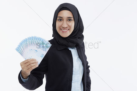 Malay : Businesswoman holding up cash