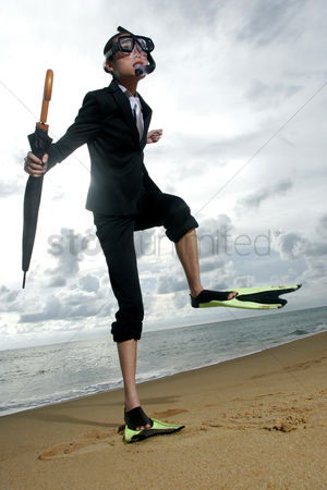 Diving : Businesswoman in flippers and snorkel walking on the beach