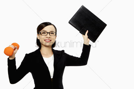 Dumbbell : Businesswoman lifting up a folder and a dumbbell