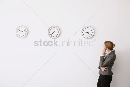 Wondering : Businesswoman looking at the time on the clocks