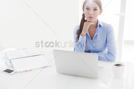 Worry : Businesswoman looking bored in front of laptop and television