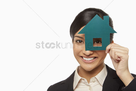 Malaysian indian : Businesswoman looking through a cut out house