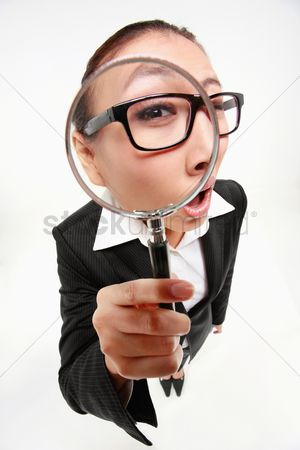 Magnifying glass : Businesswoman looking through a magnifying glass