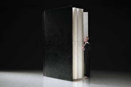 Black background : Businesswoman peeking from behind the pages of a book