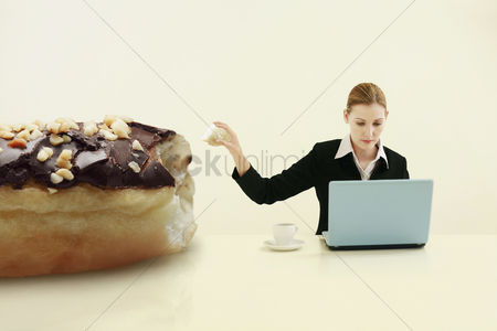 Technology background : Businesswoman pulling out a chunk of doughnut while using laptop