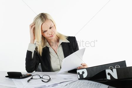 British ethnicity : Businesswoman scratching head while reading documents