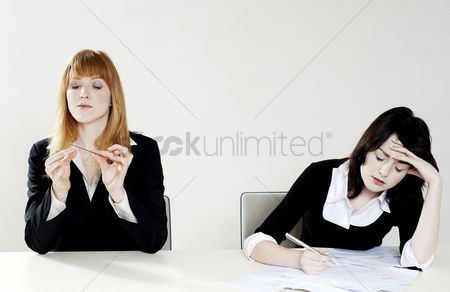 Pressure : Businesswoman shaping her fingernail while her colleague is busy doing her work