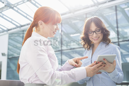 Showing : Businesswoman showing something on tablet pc to colleague in office