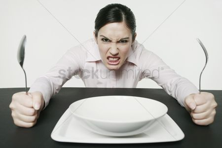 Asian : Businesswoman sitting at table looking angry