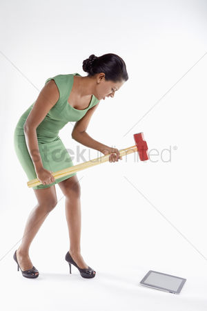 Femininity : Businesswoman smashing digital tablet with a hammer