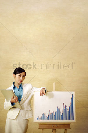 Determined : Businesswoman standing beside a chart