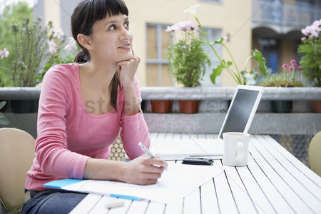 Smiling : Businesswoman thinking and drawing with white laptop in city garden
