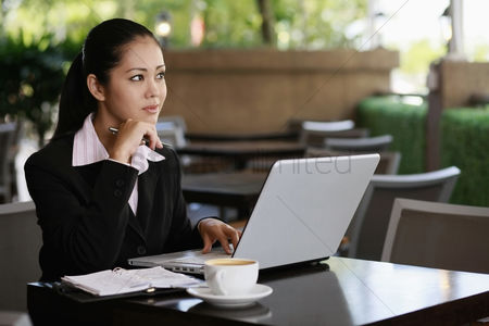 Contemplation : Businesswoman thinking while using laptop