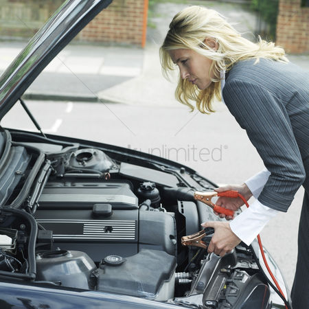 Expertise : Businesswoman using jumper cables