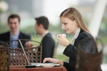 Eastern european ethnicity : Businesswoman using laptop and enjoying coffee at outdoor cafe