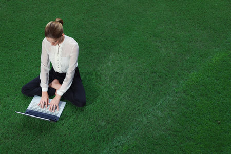 Grass : Businesswoman using laptop on the field