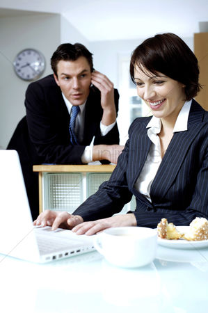 Husband : Businesswoman using laptop with her husband talking on the phone in the background