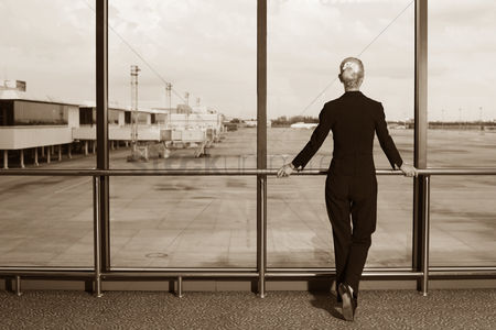 Business suit : Businesswoman waiting for her flight in airport lounge