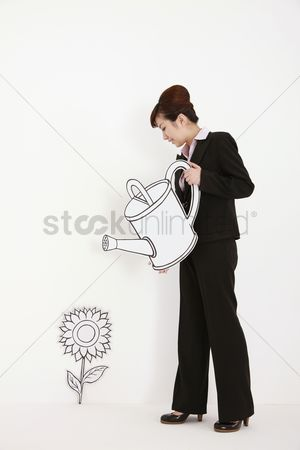 Cardboard cutout : Businesswoman watering plant with watering can