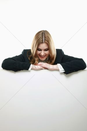 Cardboard cutout : Businesswoman with both arms resting on blank placard  looking down