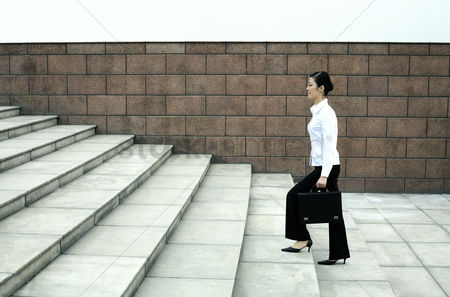 Steps : Businesswoman with briefcase walking up the stairs
