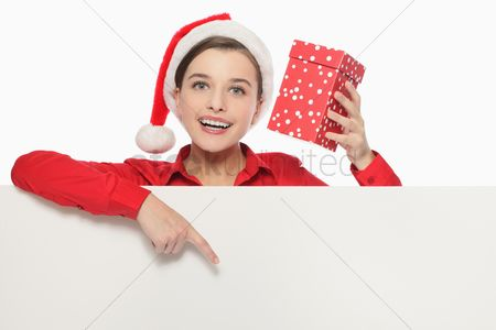 Creativity : Businesswoman with santa hat holding present and pointing at white board