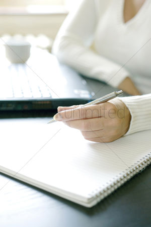 Lady : Businesswoman writing on a book while using laptop
