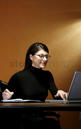 Bespectacled : Businesswoman writing while using laptop