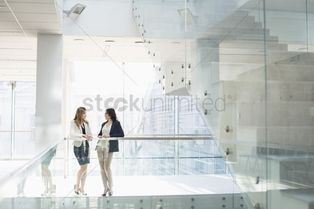 Businesswomen : Businesswomen conversing against railing in office