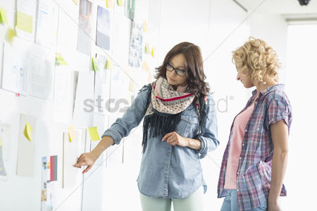Creativity : Businesswomen discussing over papers stuck on wall in creative office