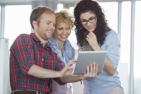 Three quarter length : Businesswomen with male colleague using tablet pc in creative office