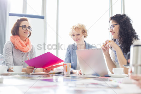 Creativity : Businesswomen working at desk in creative office
