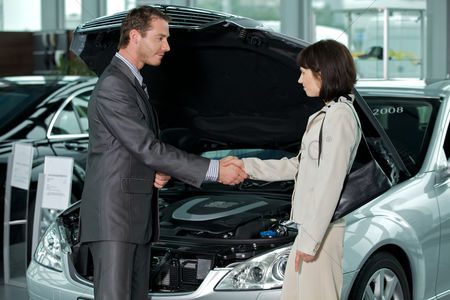 Transportation : Car salesperson shaking hands with customer at showroom