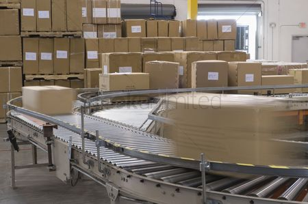 Interior : Cardboard boxes on conveyor belt in distribution warehouse
