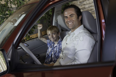 Land : Cheerful boy sitting in car with his father