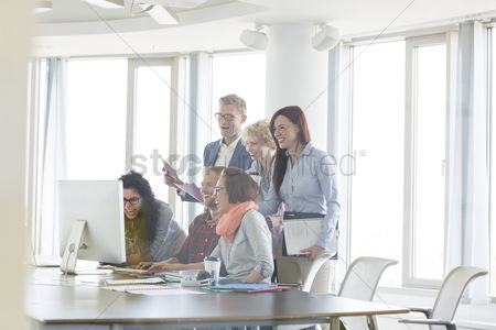Three quarter length : Cheerful businesspeople working together at conference table