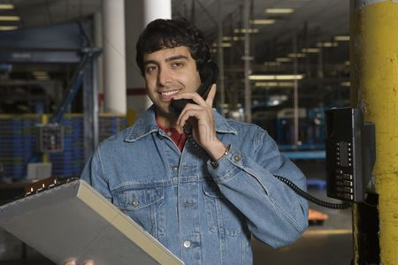 Notepad : Cheerful man using telephone in factory