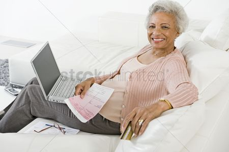 Three quarter length : Cheerful senior woman using laptop