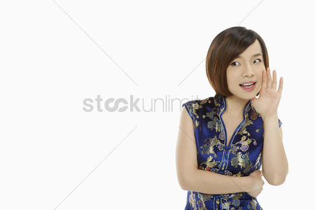 Traditional clothing : Cheerful woman in traditional clothing showing a whispering hand gesture