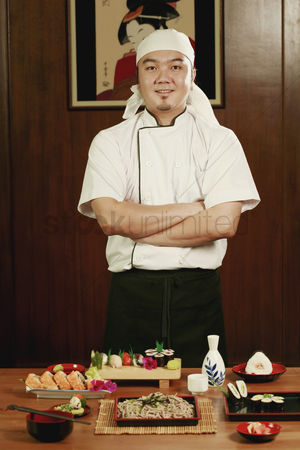 Selection : Chef standing in front of served food with his hands folded